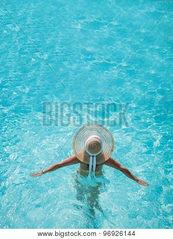 Young woman in bikini wearing a straw hat at the swimming pool