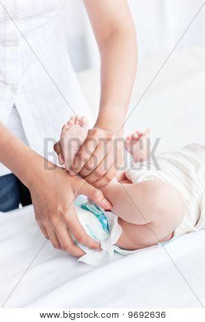 Close-up de uma mãe atenta, tirar a fralda suja de seu bebê deitado no quarto