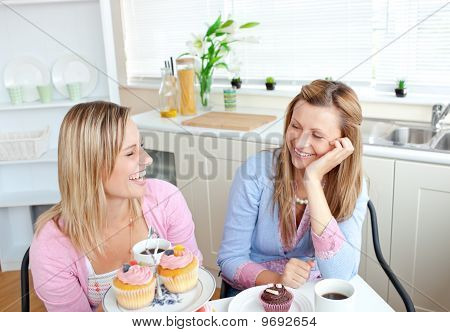 Laughing Women Eating Cupcakes And Drinking Coffee Sitting In The Kitchen