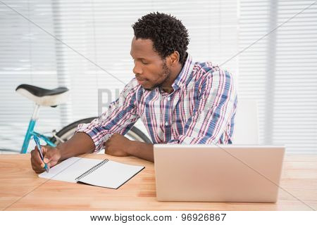 Young businessman writing on a notepad in front of a laptop in the office
