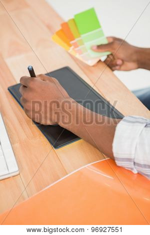 Young businessman writing on the graphic tablet at his desk in the office