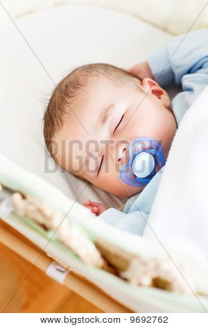 Portrait Of A Sleeping Baby Lying In His Cradle  With His Dumm