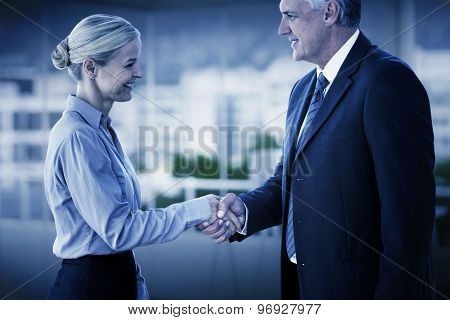 Business people shaking hands against office