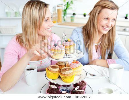 Mulheres se divertindo comendo biscoitos na cozinha