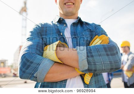 building, construction and people concept - close up of of smiling builder with crossed hands in gloves outdoors