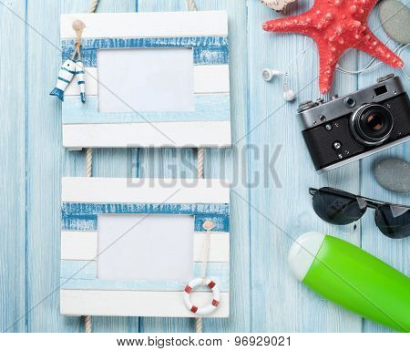 Travel and vacation photo frames with items over wooden table. Top view with copy space