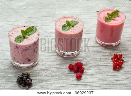 Fresh milk, currant, raspberry and red currant drinks on wodeen table, assorted protein cocktails wi