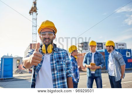 business, building, teamwork, gesture and people concept - group of smiling builders in hardhats showing thumbs up at construction site