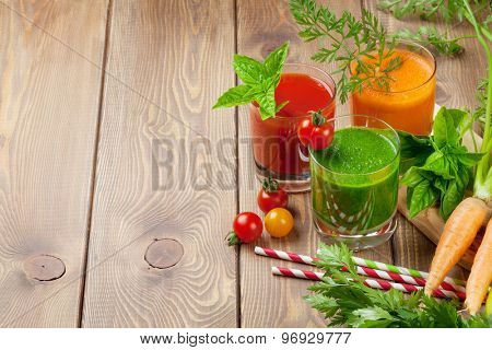 Fresh vegetable smoothie on wooden table. Tomato, cucumber, carrot.