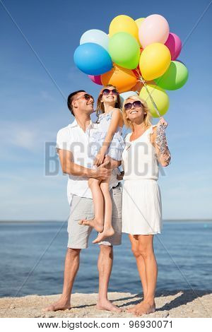 summer holidays, celebration, children and people concept - happy family with colorful balloons at seaside