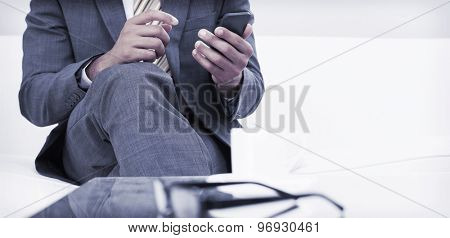 Mid section of an elegant young businessman text messaging on sofa at home