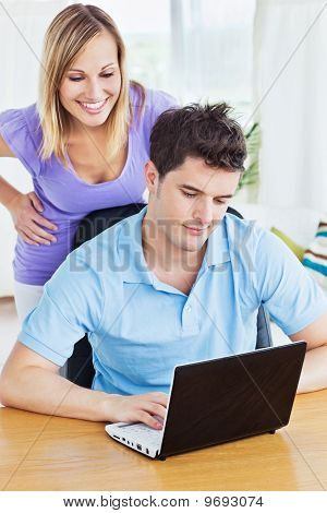 Serious Man Using His Laptop With His Girlfriend Behind Him Watching His Work
