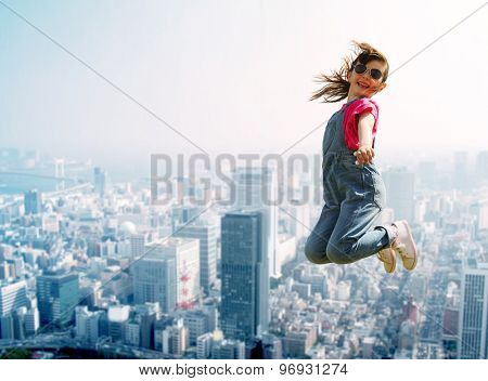 summer, childhood, leisure and people concept - happy little girl jumping high over city background
