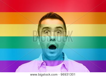homosexual, homophobia, intolerance, emotions and people concept - shocked gay man shouting over rainbow flag background