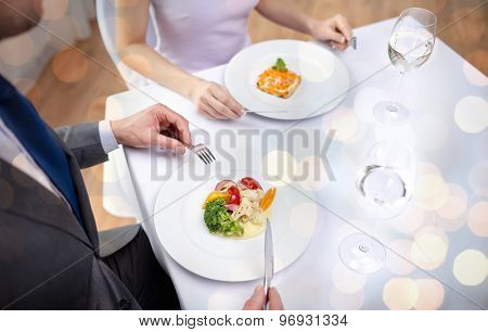 restaurant, food, people, date and holiday concept - close up of couple eating appetizers at restaurant over holidays lights background