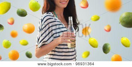 summer vacation, holidays, drinks and people concept - close up of smiling young woman drinking from bottle over fruits and berries on gray background