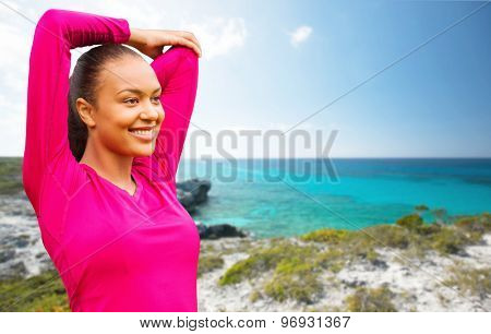 fitness, sport, training, exercising and people concept - smiling woman stretching hand over background