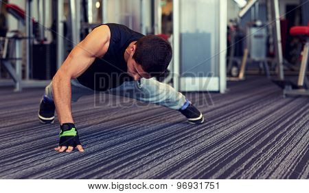 fitness, sport, people and lifestyle concept - man doing one arm push-ups in gym