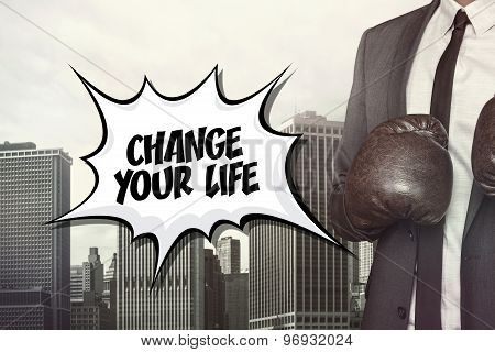 Change your life text with businessman wearing boxing gloves
