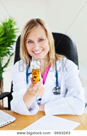 Attractive Female Doctor Showing Pills To The Camera Sitting In Her Office