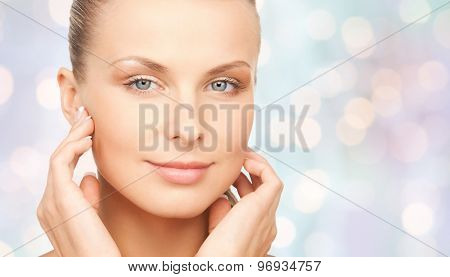 beauty, people and body care concept - beautiful young woman touching her face over blue holidays lights background