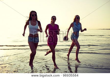summer vacation, holidays, travel and people concept - group of smiling young women in sunglasses and casual clothes running on beach