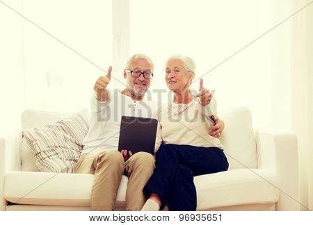family, technology, age, gesture and people concept - happy senior couple with tablet pc computer showing thumbs up at home