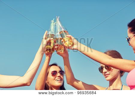 summer vacation, holidays, party, travel and people concept - close up of happy young women with drinks clinking bottles