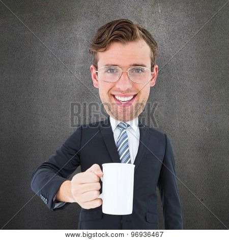 Geeky businessman holding mug against grey room