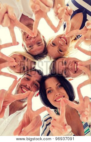 friendship, happiness and people concept - smiling friends in circle showing victory sign