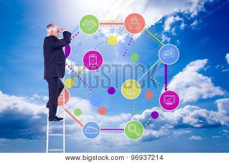 Mature businessman standing on ladder against blue sky