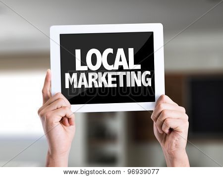 Tablet pc with text Local Marketing on a house background
