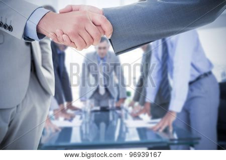 Business handshake against business colleagues discussing about work