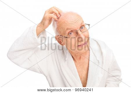 Senior man in a white bathrobe checking his hair isolated on white background