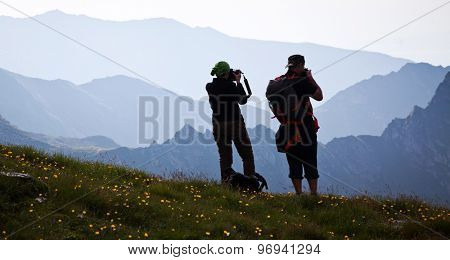 Couple of hikers admiring view and taking photographs of surrounding mountains