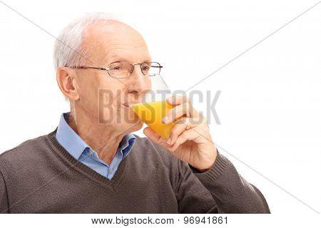 Studio shot of a senior drinking an orange juice isolated on white background