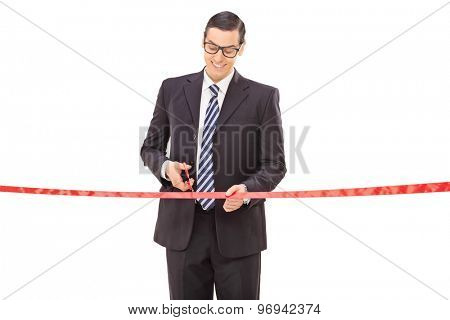 Joyful young businessman cutting a red ribbon with scissors isolated on white background