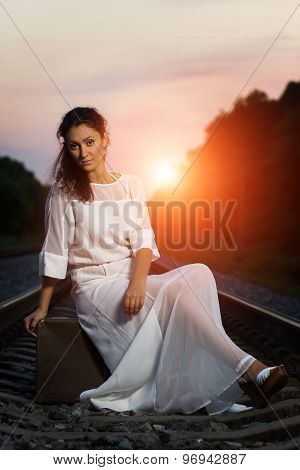 Pretty Young Woman With Old Suitcase Sitting At The Railway