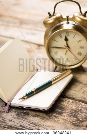 Open Small Notebook With Fountain Pen And Old-fashioned Alarm Clock Behind
