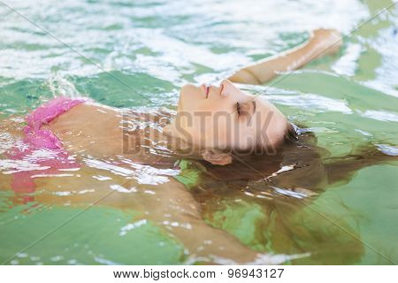 Young Woman Relaxing In The Water In The Pool