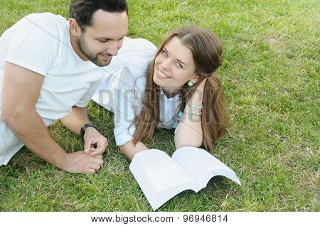 Couple Of Young Students Studing On The Grass By The Campus