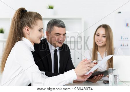 Two Young Beautiful Business Women Consulting With Their Colleague