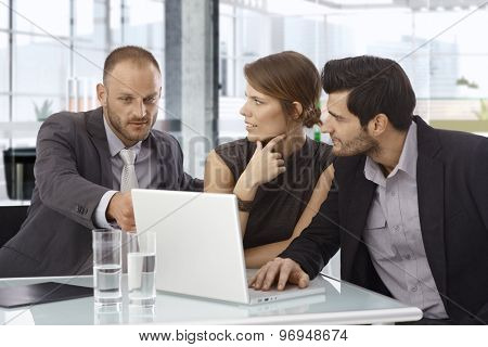 Small businessteam working together, using laptop computer, sitting at table.