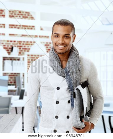 Portrait of stylish young black man holding bag, smiling, looking at camera.