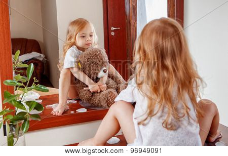 Portrait of little girl with teddy bear looking through near mirror