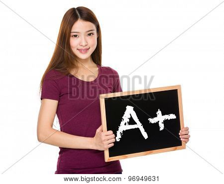 Young student hold with chalkboard showing A plus mark