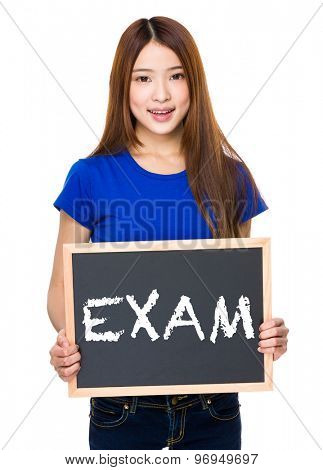 Young woman with black board showing a word exam