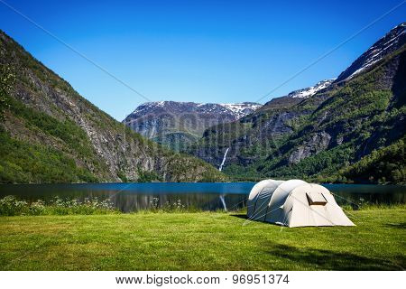 Camping. Holiday in Norway. Tourist tent on the shore of the lake.