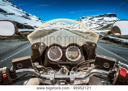 Biker rides a motorcycle on a slippery road through a mountain pass in Norway. Around the fog and snow. First-person view.