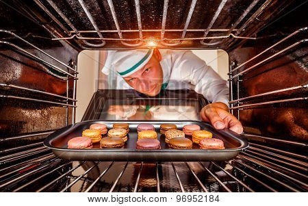 Chef prepares macarons in the oven, view from the inside of the oven. Cooking in the oven.